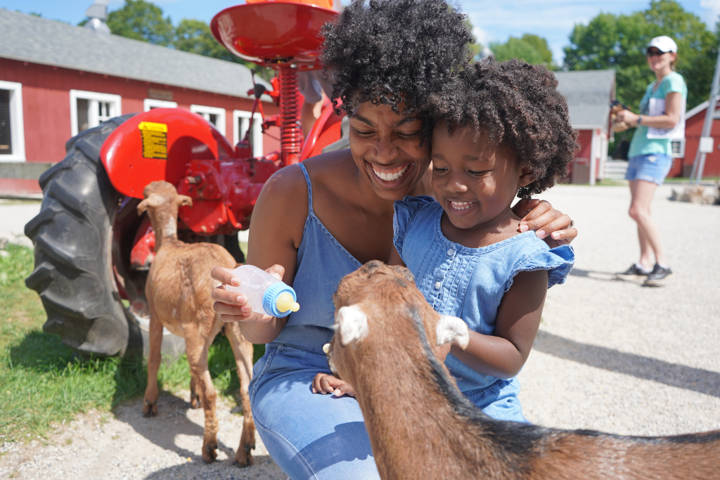 Mom and daughter feeding a baby goat as one of their things to do in door county with kids.
