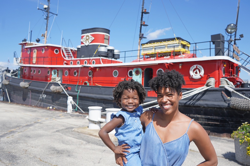 Mom and daughter stand outside a tug boat