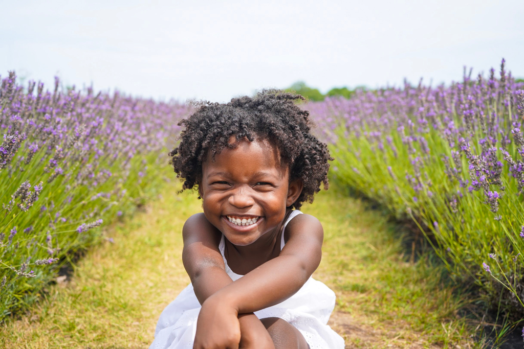 A little girl in a white dress posing for a picture on a lavender farm