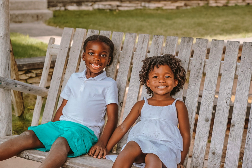 Little boy and girl sitting on a swing smiling and holding hands.