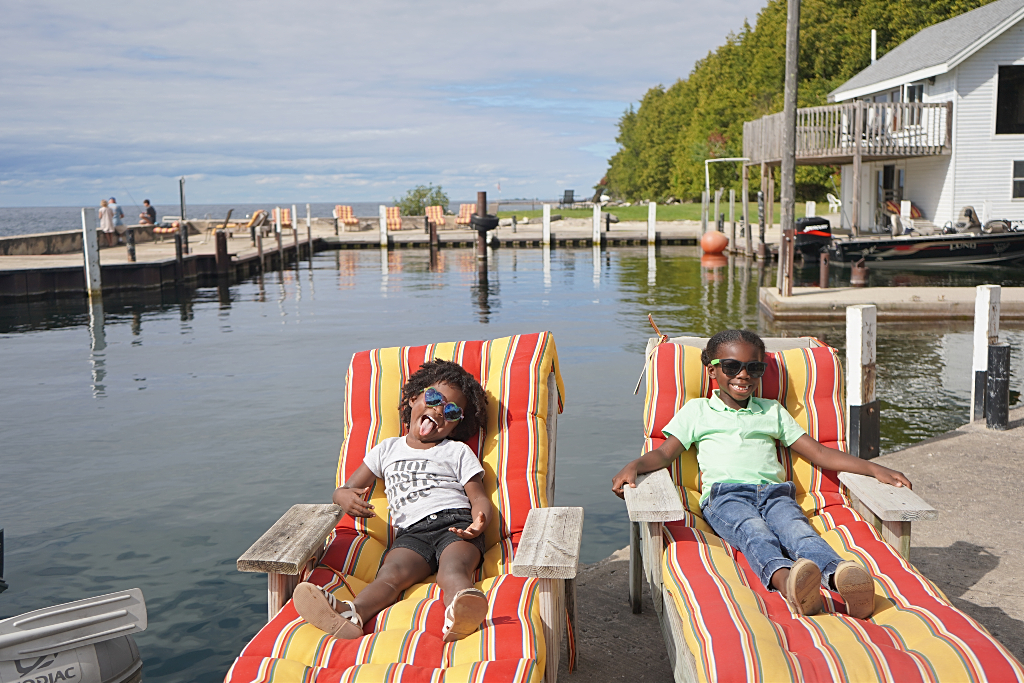 A little boy and girl sit on red and yellow stripped lounge chairs by lake Michigan.