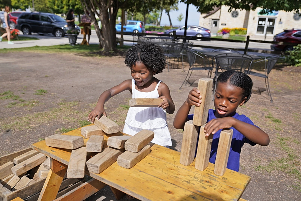 A boy and a girl outside playing with wooden building blocks.