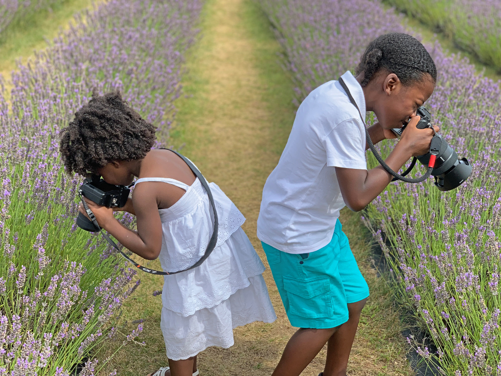 A boy and a girl both taking up close pictures of lavender.