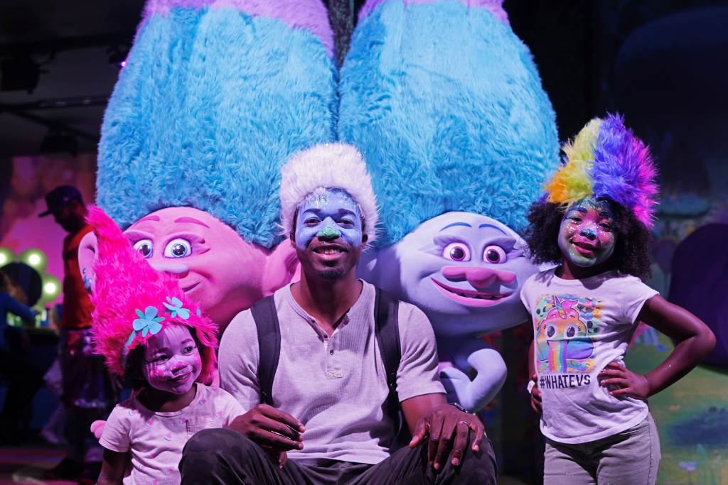 dad and two daughters transform into characters from Trolls and Trolls the Experience in New York