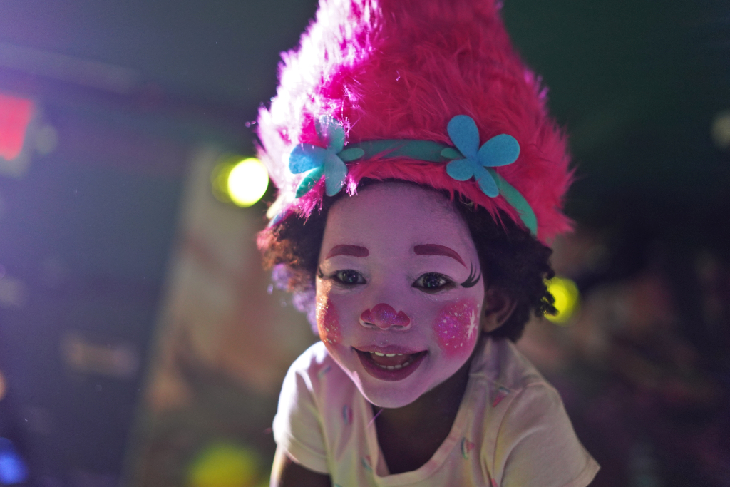 little girl who went to Trolls the Experience and transformed into the character Princess poppy with a pink face and pink wig