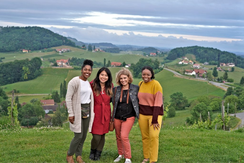 Four friends stand together on a hill side in Austria smiling happily at the camera enjoying their cheap European vacation.