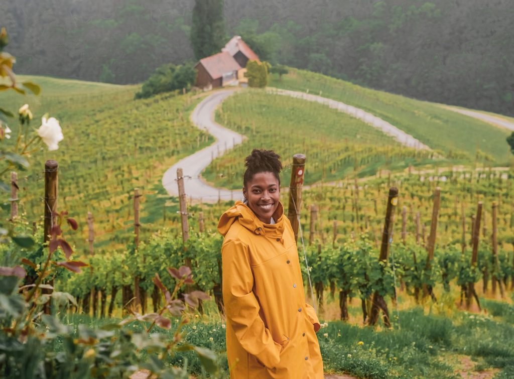 A woman standing in a field in Austria with a house on a hill in the background enjoying her cheap European vacation