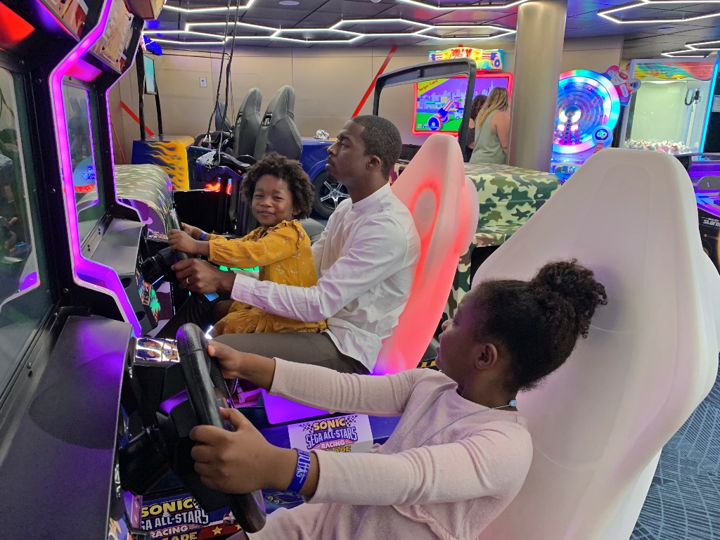 dad playing with two daughters in the arcade on Navigator of the Seas cruise ship racing each other on a racing game