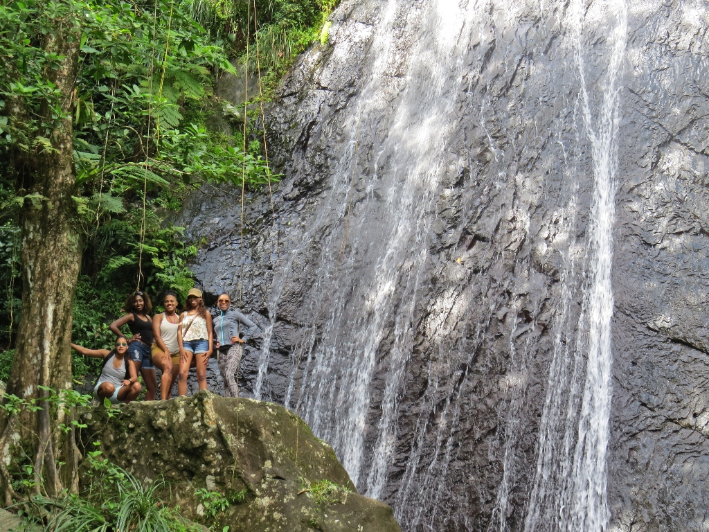five friends standing on a rock near a waterfall on a hike in puerto rico
