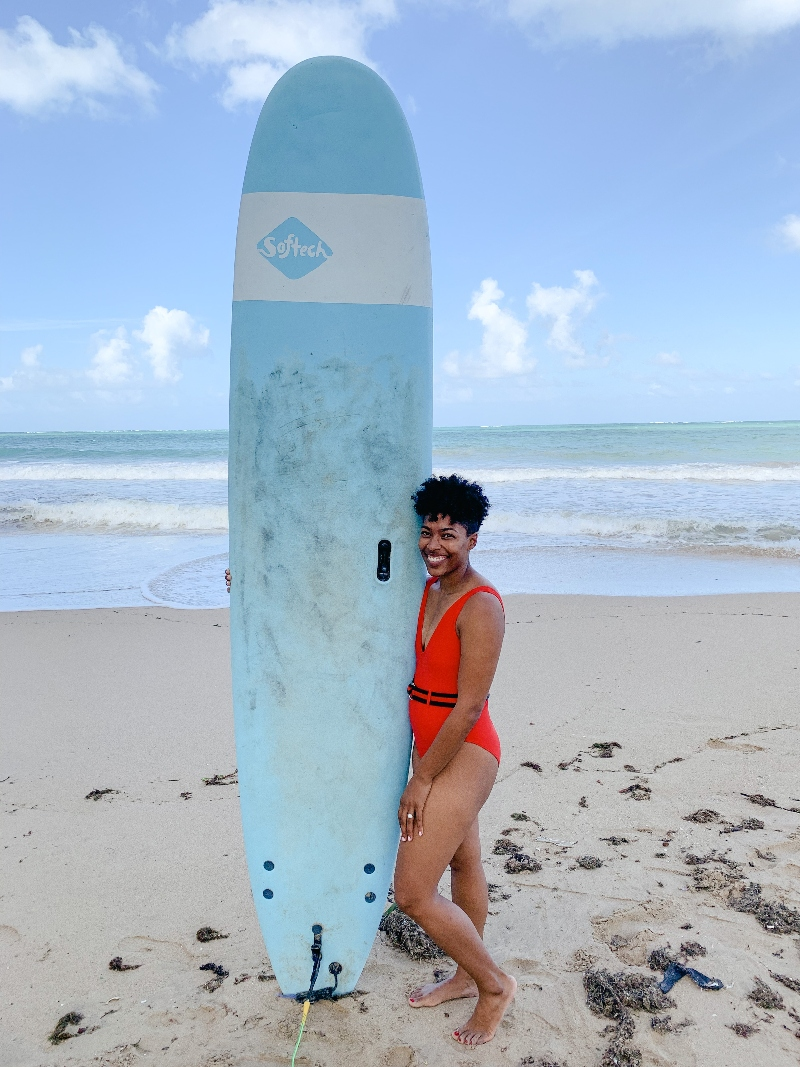 girl in red swimsuit on the beach holding up a blue surf board in San Juan Puerto Rico