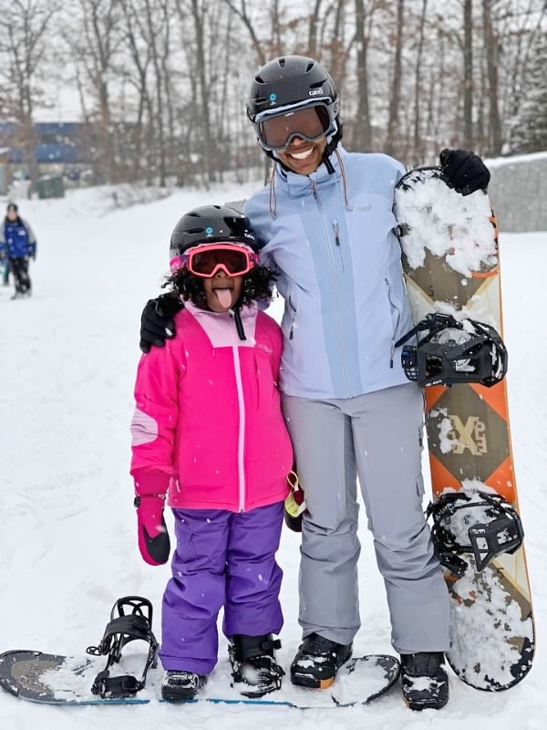 Mother and young daughter snowboarding