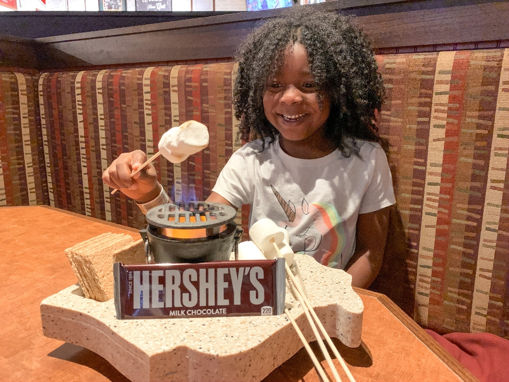 little girl at table making s'mores