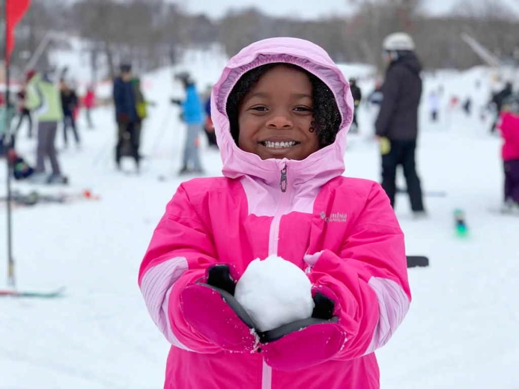 Little girl holding a snowball in her hand