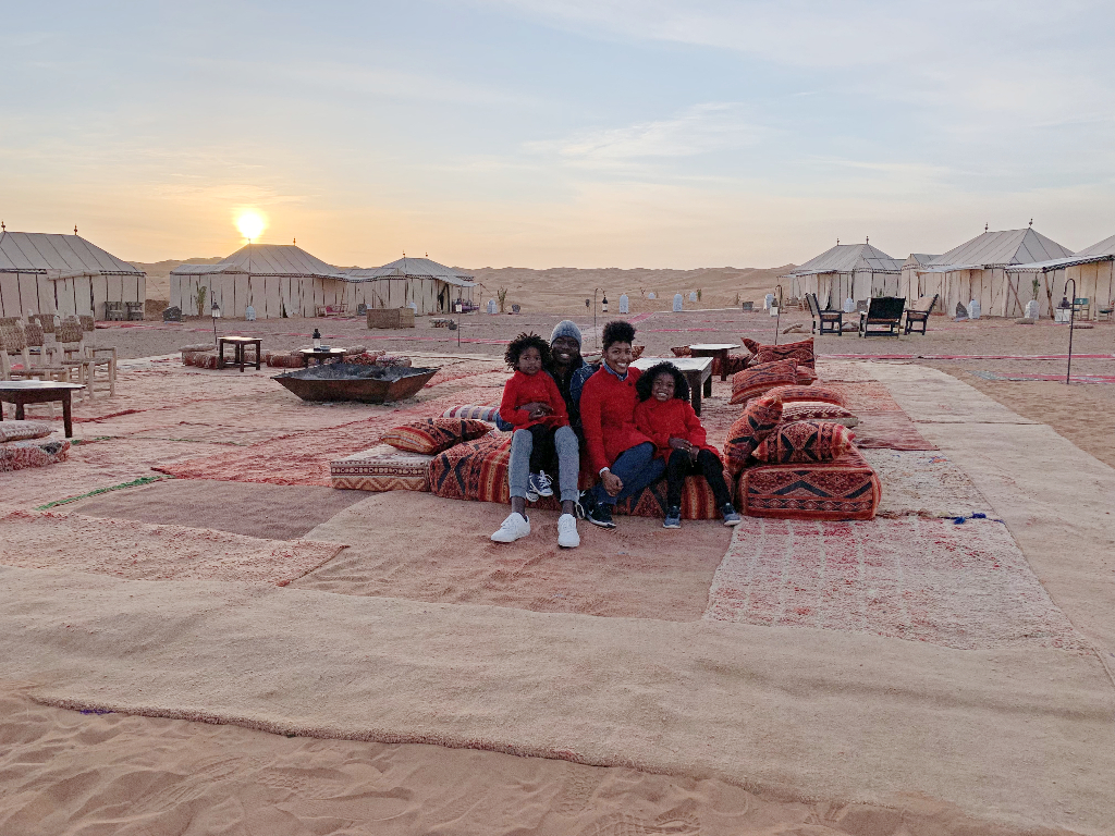 family of four two adults and two daughters sitting in the middle of a tent camp in the sahara desert with the sunrise in the background