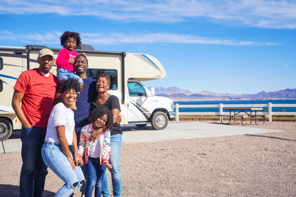 family of grandparents, parents, and children (total of 6) standing in front of RV during their Nevada road trip