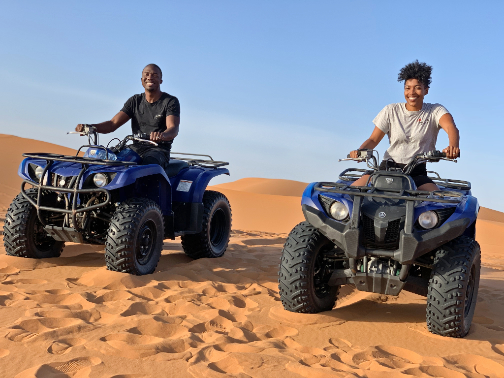 a man and women on two ATVs riding through sand dunes in the Sahara desert