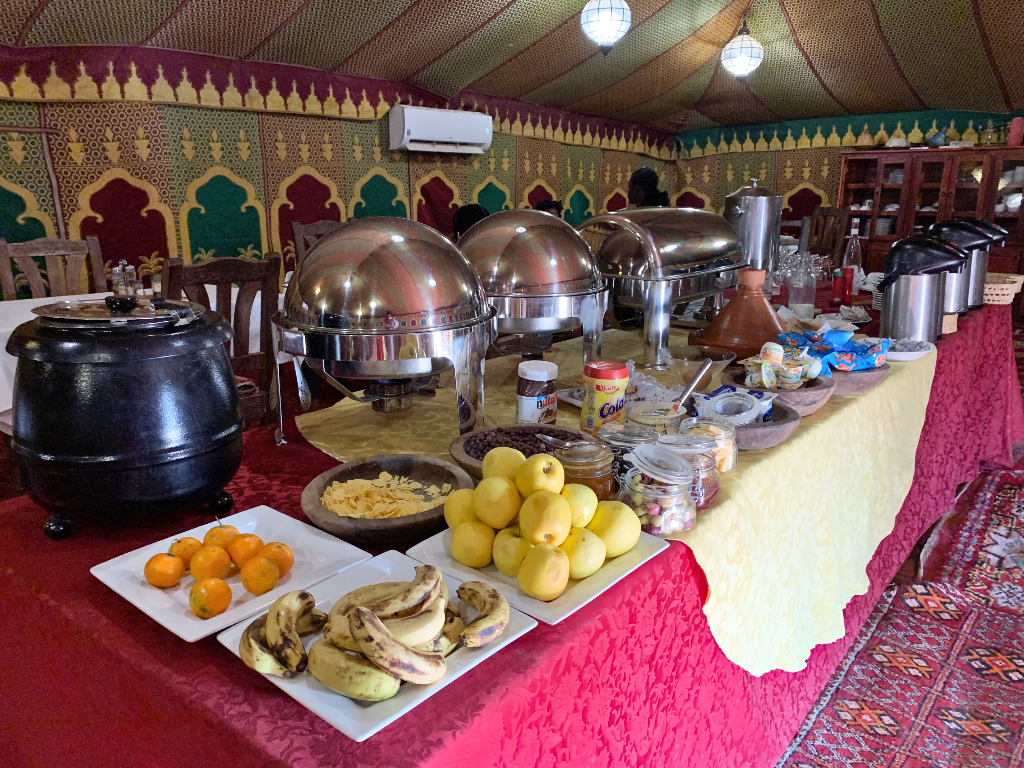 Breakfast Buffet at Desert Luxury Camp table filled with plates of fruit like bananas apples and oranges, stay warm containers with eggs and coffee pots