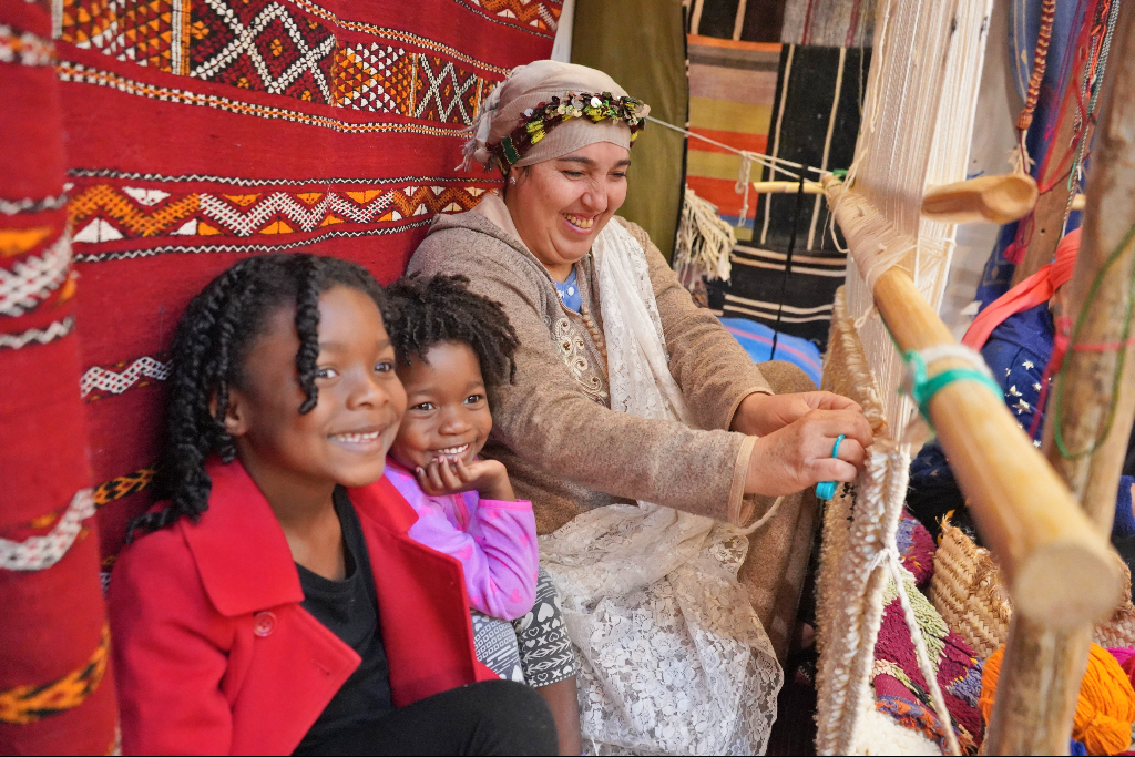 two young girls being taught how to make a carpet at a berber house on a Sahara desert tour