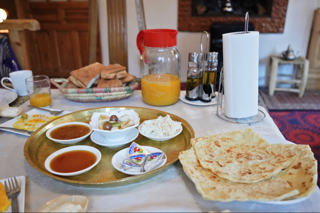 Breakfast spread of Moroccan crepes, fried eggs, hard boiled eggs, bread, cheese, butter and jam.