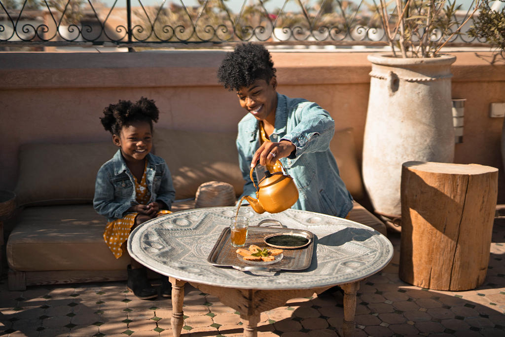 mom and daughter in matching yellow dresses and jean jackets having tea on the rooftop of le riad yasmine in marrakech
