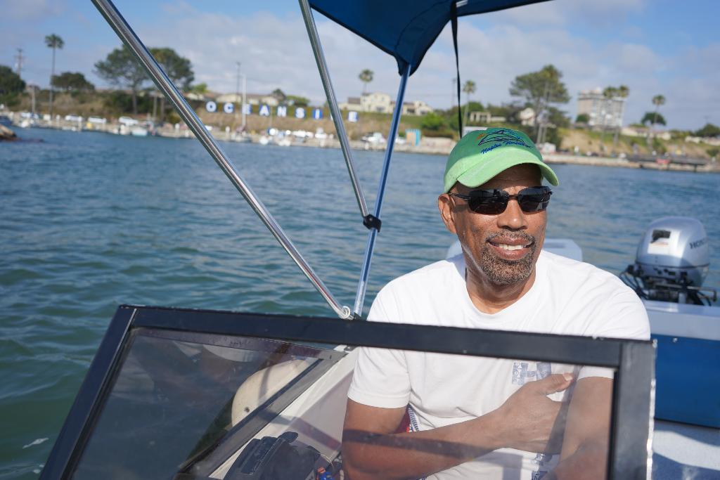 black man driving a boat