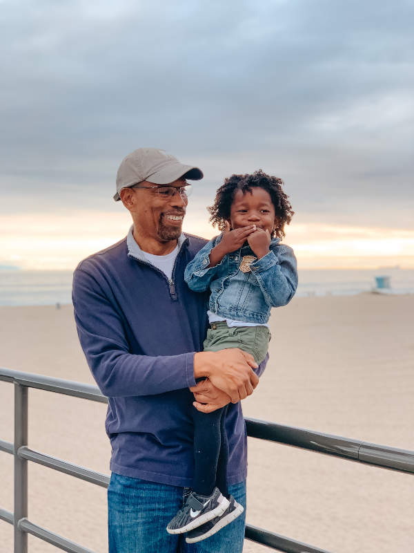black family travel grandfather holding grand daughter while standing on a pier as the sun sets behind them