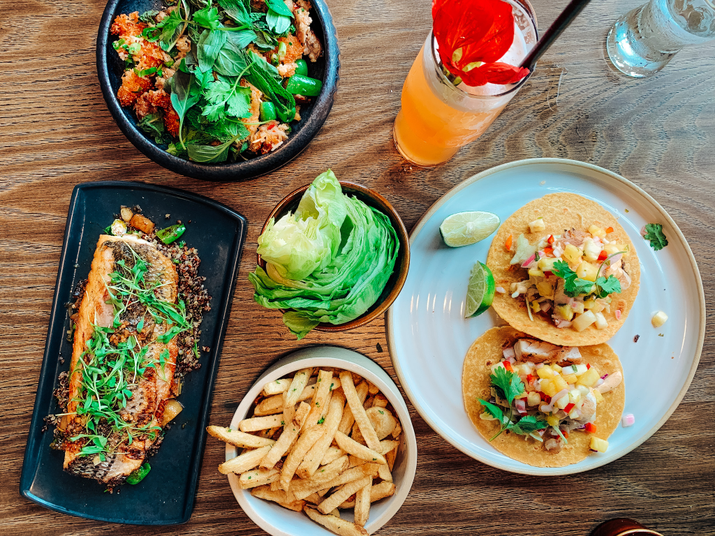 lunch spread of fish, tacos, fries, lettuce wraps and a drink