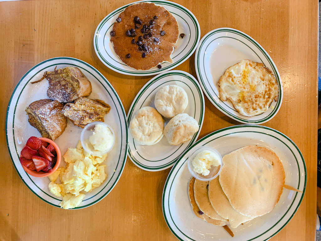 table with plates of pancakes, french toast, eggs, biscuits, and strawberries
