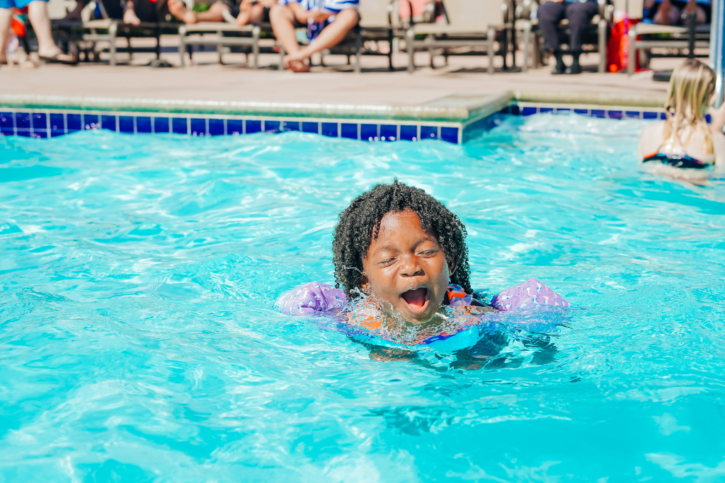 family travel black girl swimming in pool with floaties on at RV park in Southern California