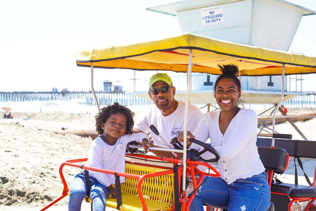 family travel black family sitting on a surrey bike on the beach boardwalk