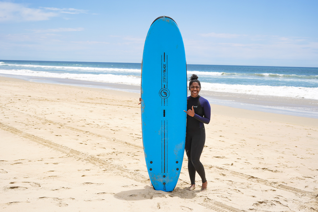 Black women standing next to a blue surf board she is holding on the beach before taking surf lessons