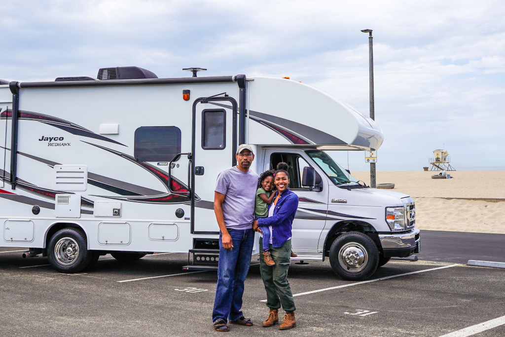 father, daughter and grand daughter standing in front of rented RV