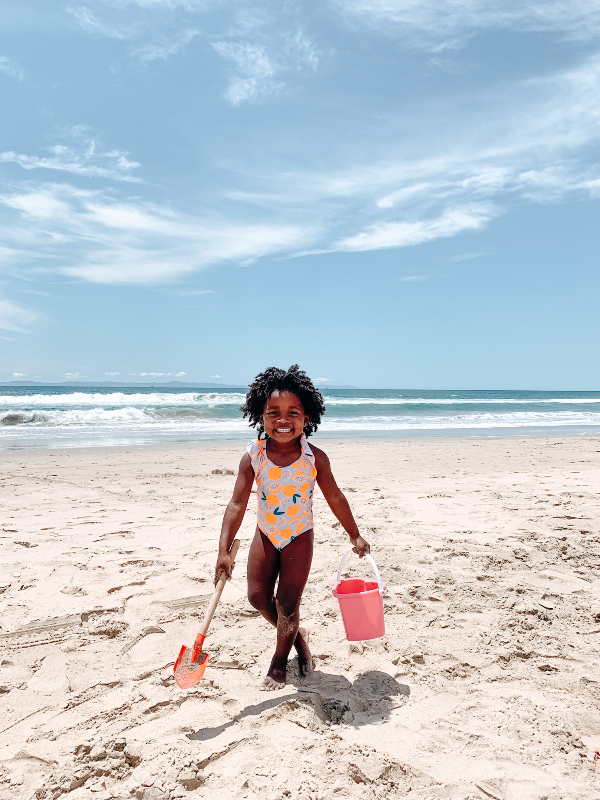 black toddler playing on the beach with a bucket and pal