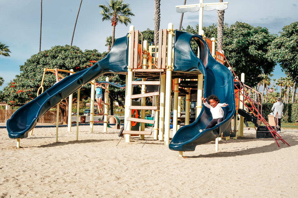 black girl going down a slide at the playground in Huntington Beach at Newport Dunes RV Resort