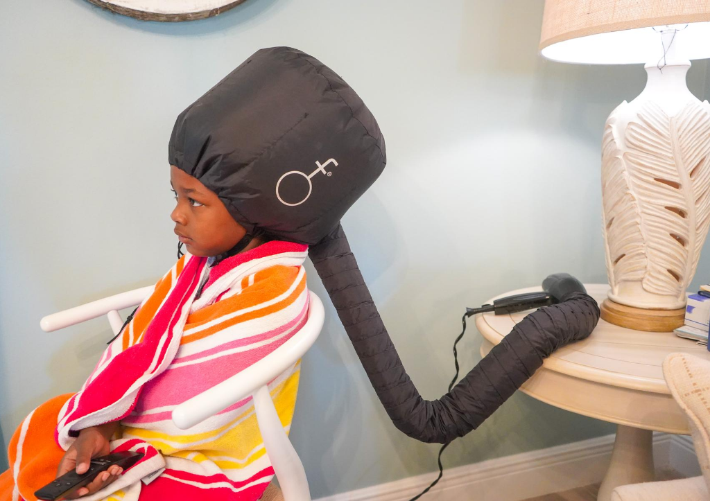 girl sitting under soft dryer getting her hair done