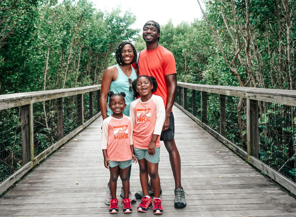 family standing on a boardwalk with trees all around wearing hiking clothes