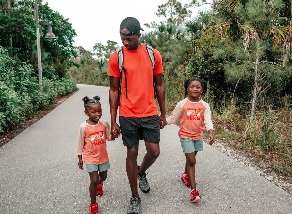 dad hiking on paved trail with two toddler daughters