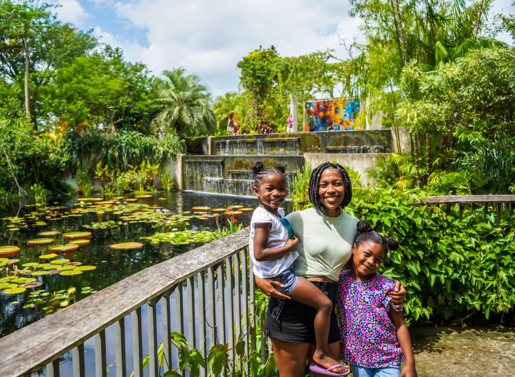mom with two daughters (hold one in her arm) with a waterfall and lake with lily pads behind them