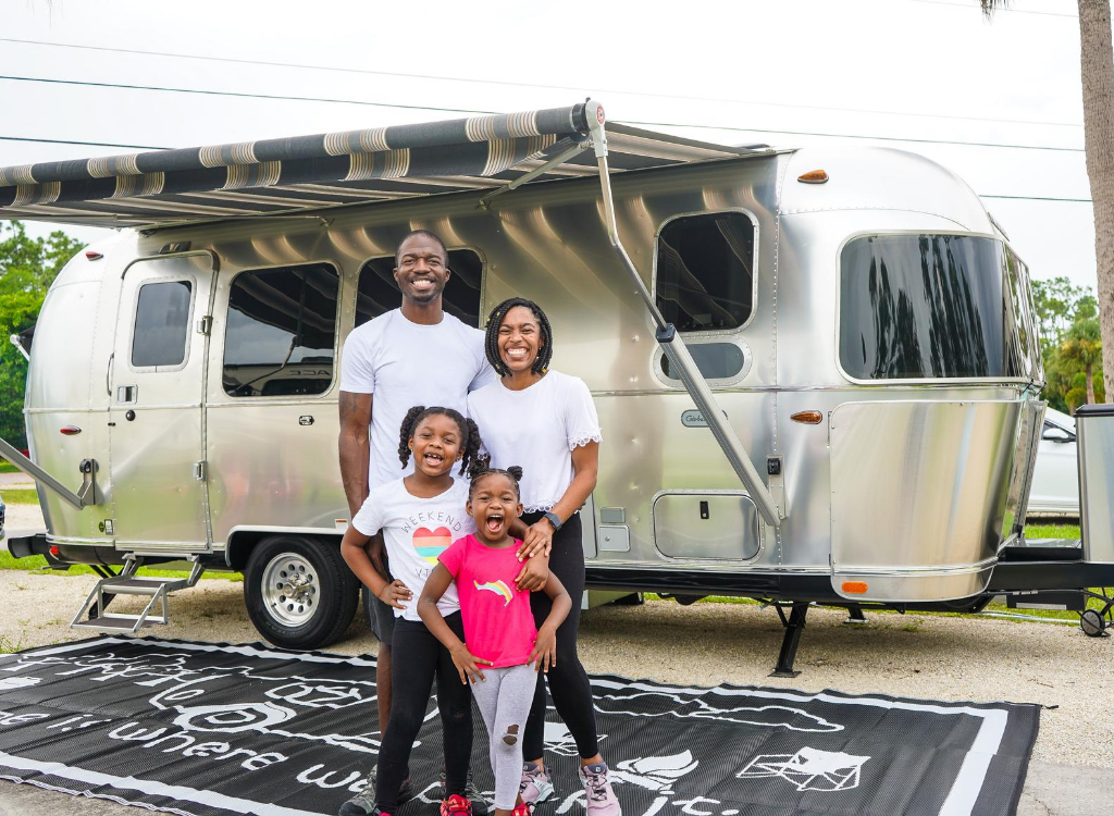 black rv family with parents and two toddler daughters standing in front of airstream