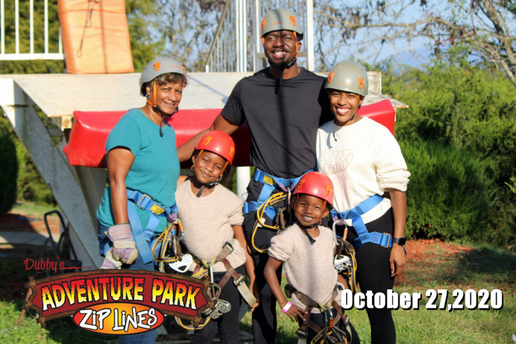 mom, dad, two girls and their grandma harnessed up to go ziplining