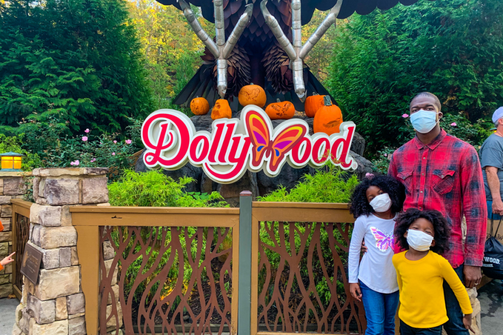 dad with two daughters at Dollywood theme park posing in front of the sign
