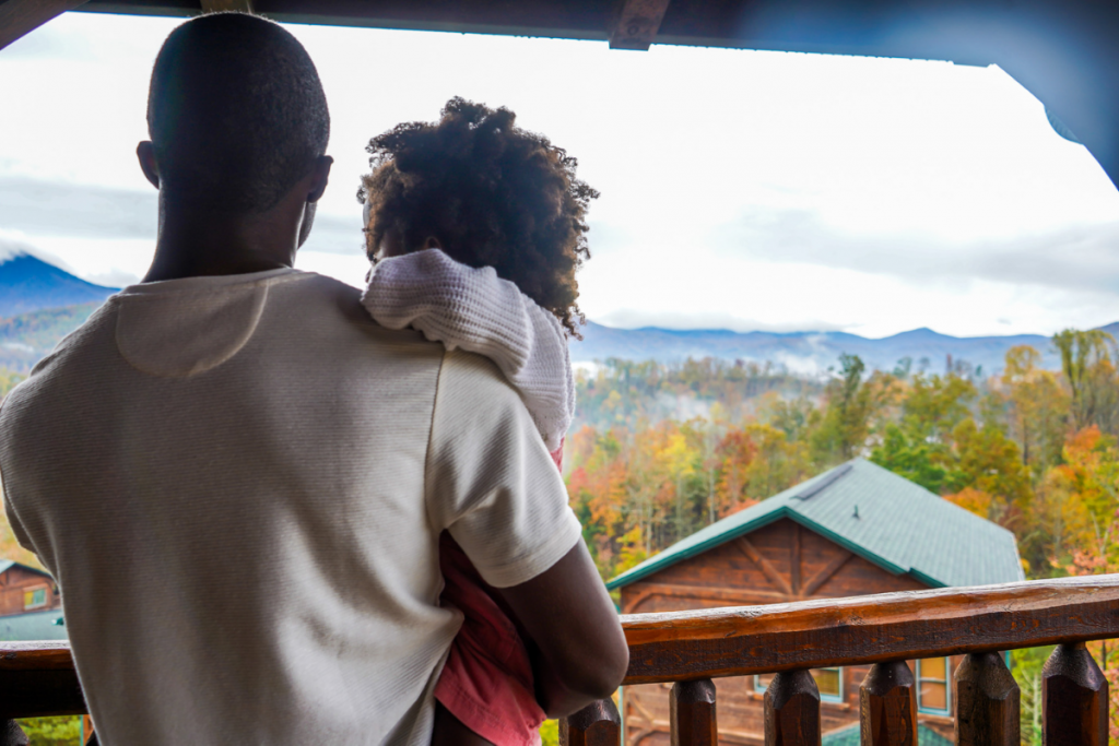 dad holding daughter on a cabin balcony looking at the views of the Smoky Mountains