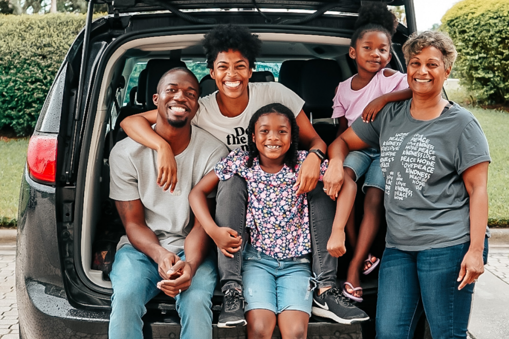 two parents with their two daughters and grandma sitting in the back of a black mini van getting ready for a road trip to franklin, tennessee