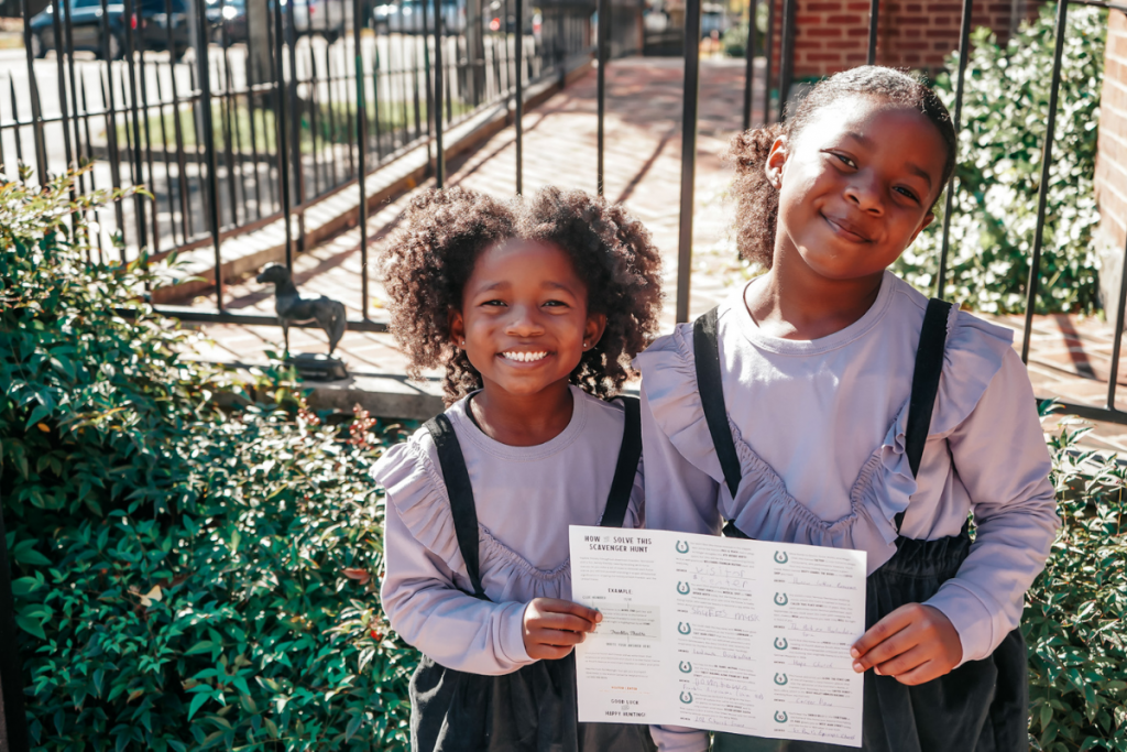 two young girls doing a scavenger hunt in franklin tennessee, holding up their completed paper