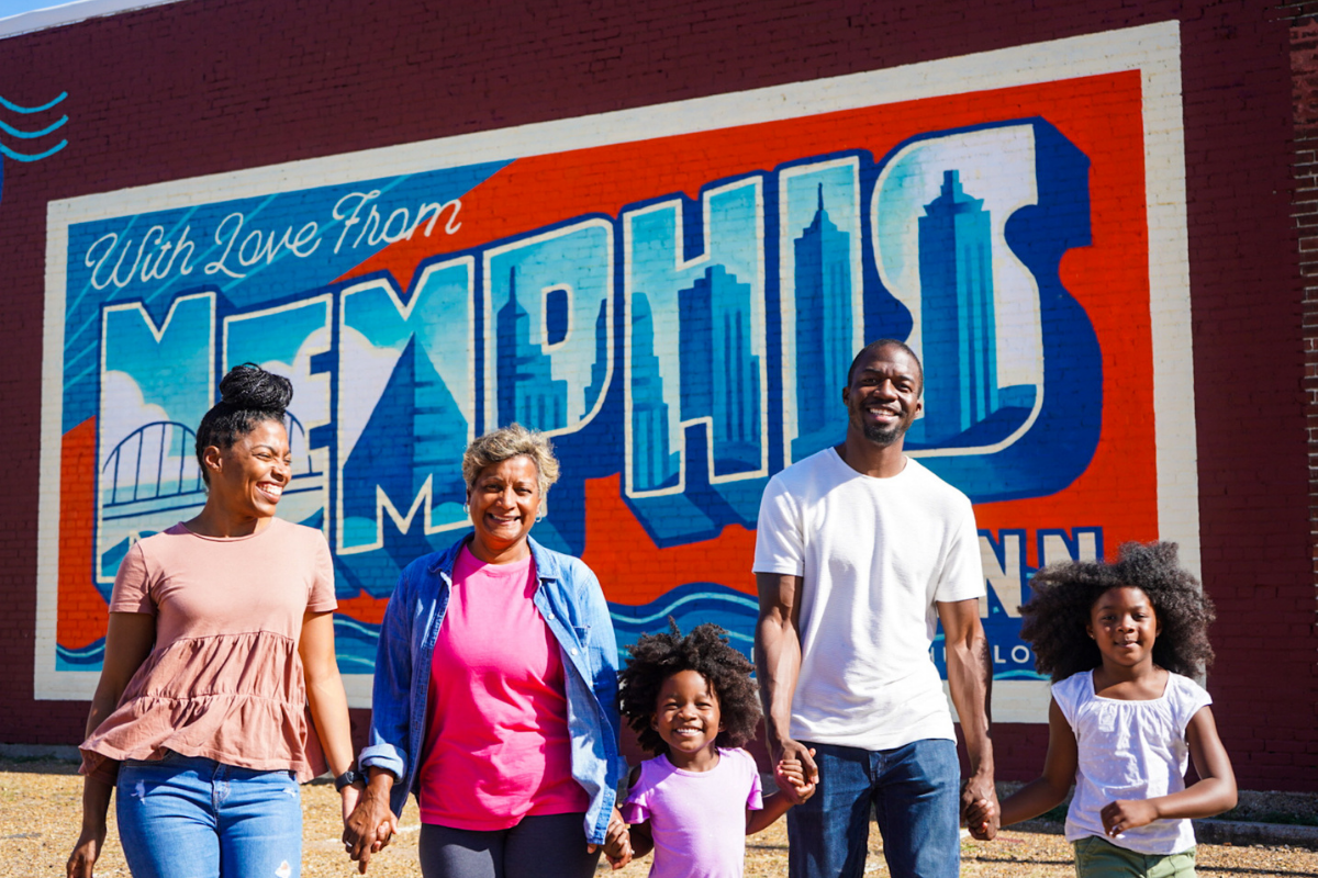 parents and kids standing in front of with love from memphis sign