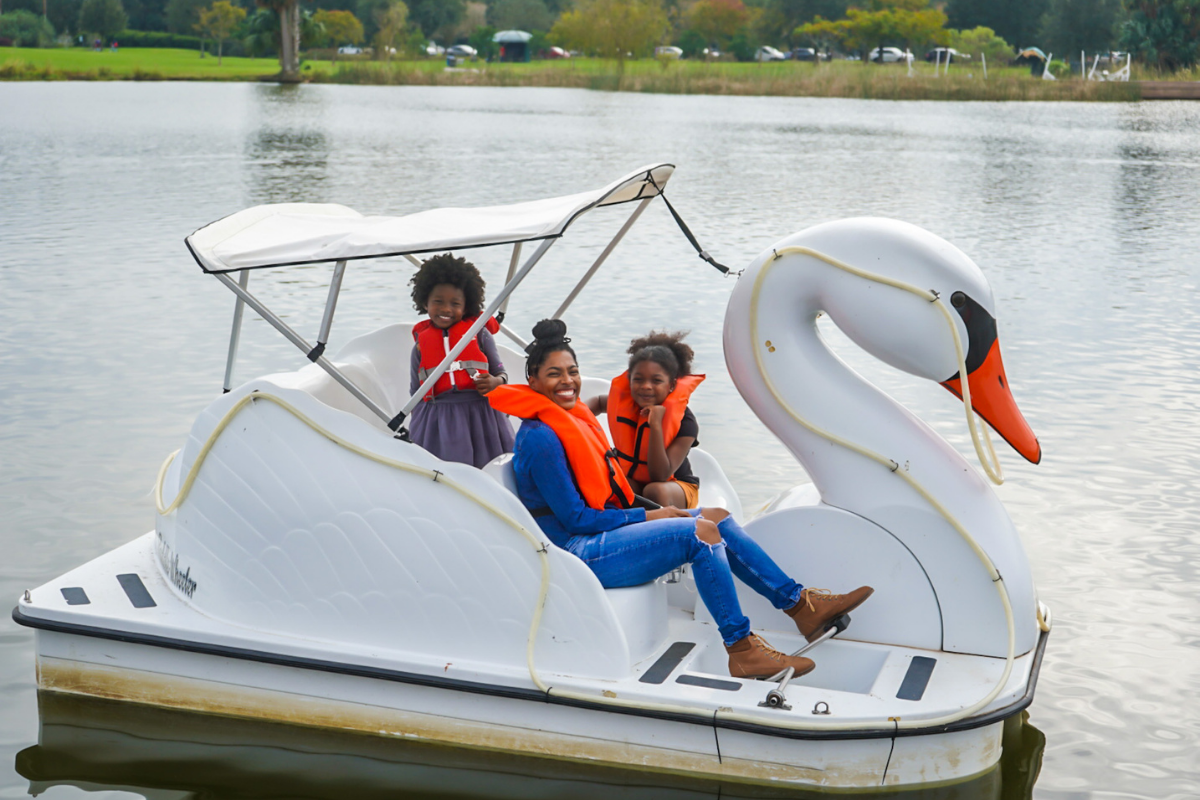 mom with two kids on swam pedal boat in city park lake