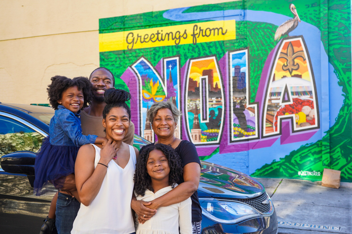 mom, dad, their two kids (girls) and grandma standing front of mini van in front of a Greetings from NOLA painting on a wall