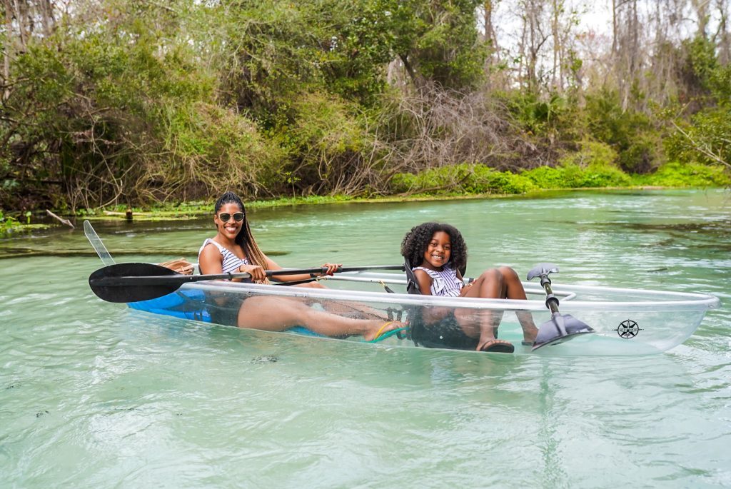 a mom and her daughter kayaking in a river enjoying a low-profile outdoor spring break