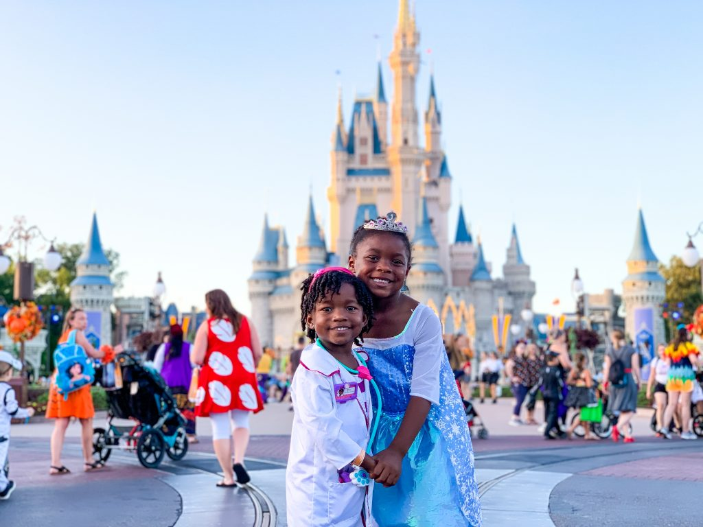 two little girls dressed up in Disney attire standing in front of the Disney world princess castle