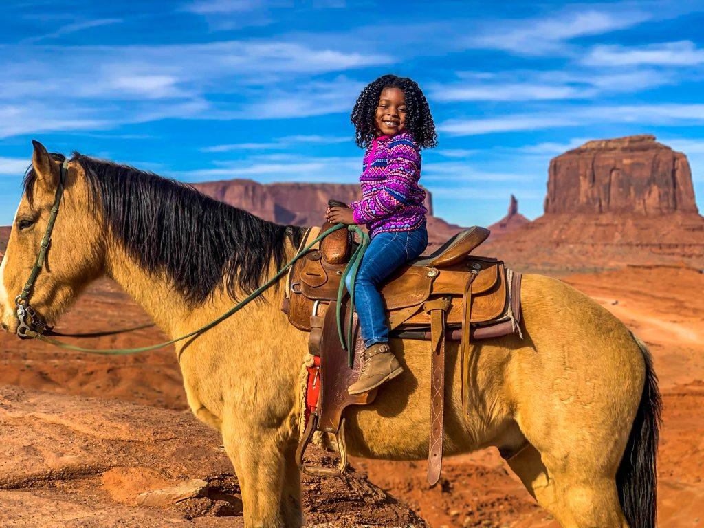 little girl riding a horse at a ranch enjoying a relaxing, low-key spring break